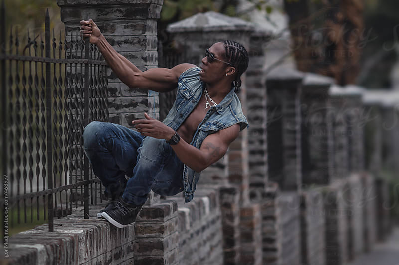 black boy hanging on the fence by Igor Madjinca for Stocksy United