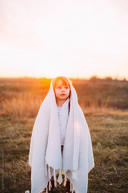 Portrait of a kid covered with white blanket. by Studio Firma for Stocksy United