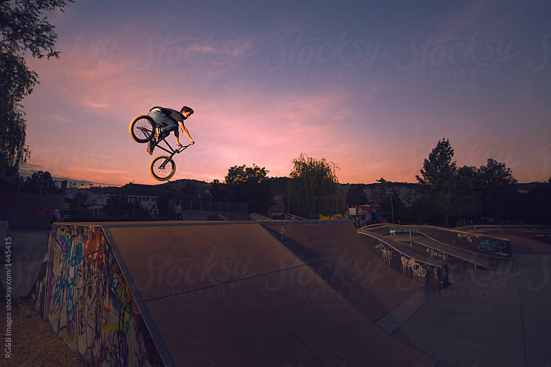 Teenager performing midair stunts with BMX against dramatic twilight sky