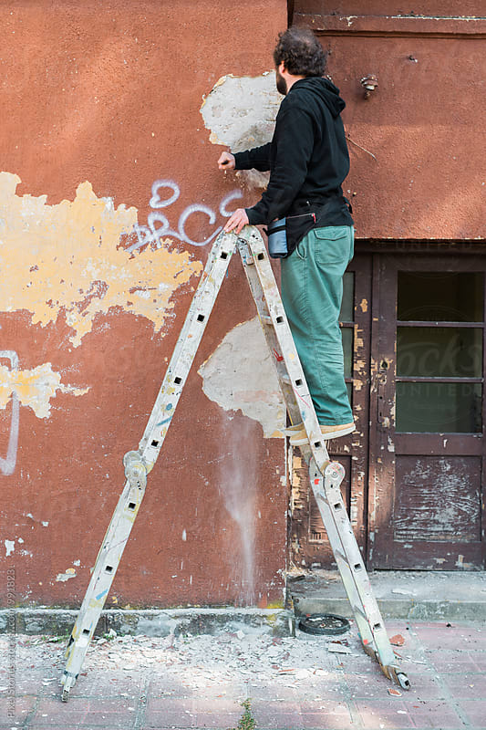 Graffiti artist preparing wall for painting by Pixel Stories for Stocksy United