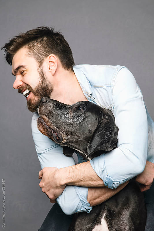 Bearded man hugging and laughing with his dog by T-REX & Flower for Stocksy United