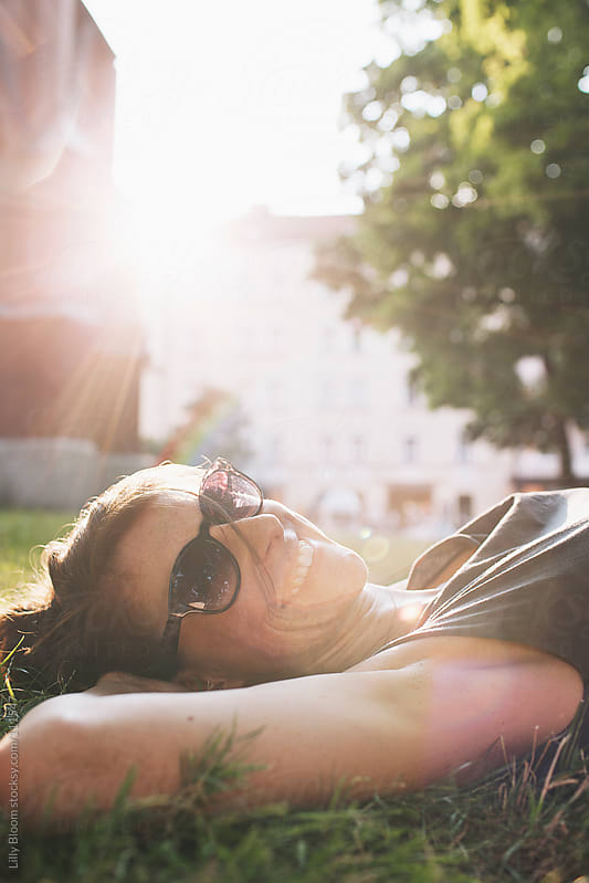 Young woman, enjoying the evening sun, lying in the grass by Lilly Bloom for Stocksy United