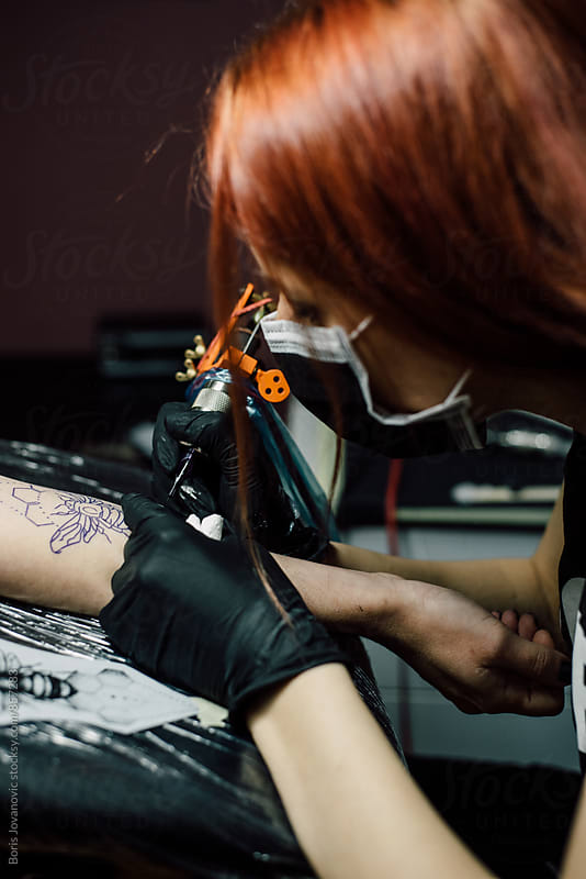 Tattoo artists doing a tattoo  by Boris Jovanovic for Stocksy United