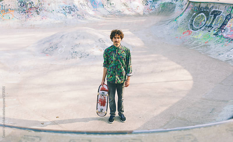 Young stylish man holding skateboard in skatepark by Denni Van Huis for Stocksy United
