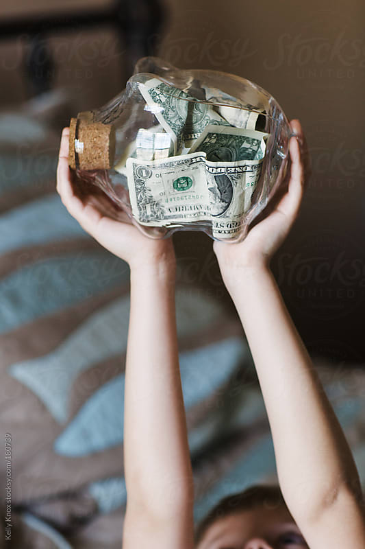 child holding a piggy bank by Kelly Knox for Stocksy United