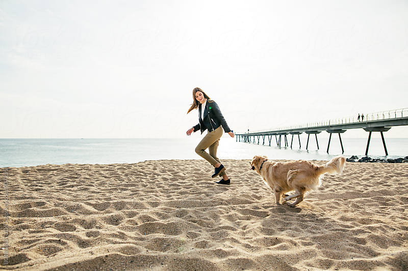 Woman playing with her dog on the beach. by BONNINSTUDIO for Stocksy United