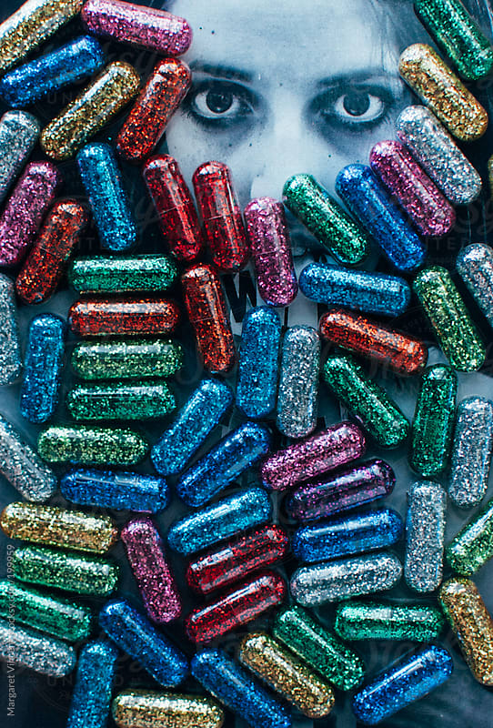 multicolor glitter pills cover a photographed face by Margaret Vincent for Stocksy United