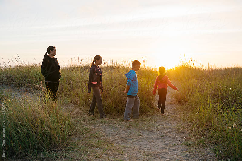 Family Walking At The Beach At Sunset by Ronnie Comeau for Stocksy United