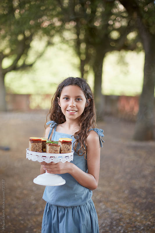 Young girl holding a plate with cakes by Miquel Llonch for Stocksy United