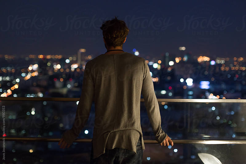 Casually dressed man looking at the city from the balcony by Jovo Jovanovic for Stocksy United