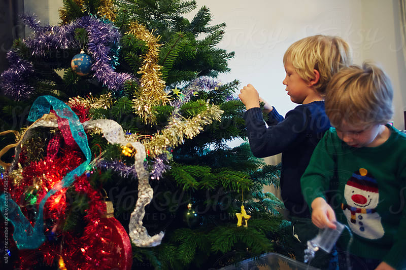 Two children decorating a Christmas tree by sally anscombe for Stocksy United