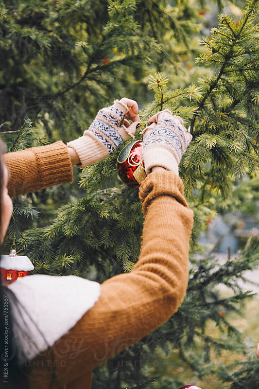 Woman's hands decorate fir tree with Christmas ball by Danil Nevsky for Stocksy United