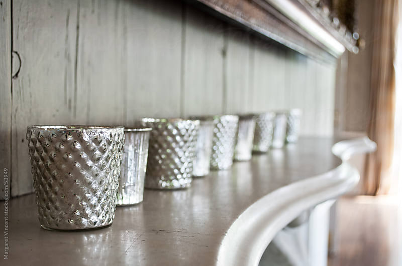a line of elegant silver cups on a marble mantle by Margaret Vincent for Stocksy United