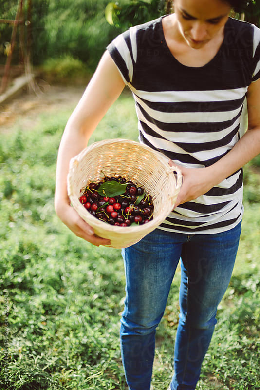 woman is holding a cherries by Jovana Vukotic for Stocksy United