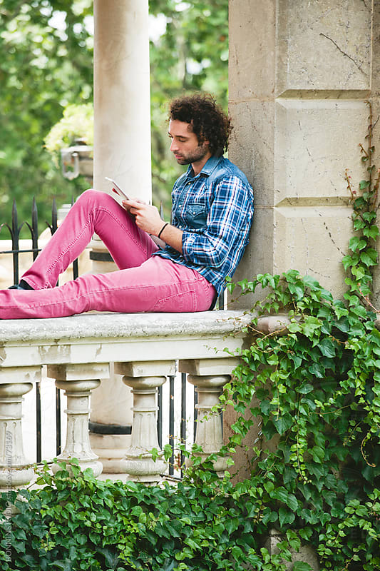 Young man with curly hair sittion on a park with digital tablet. by BONNINSTUDIO for Stocksy United