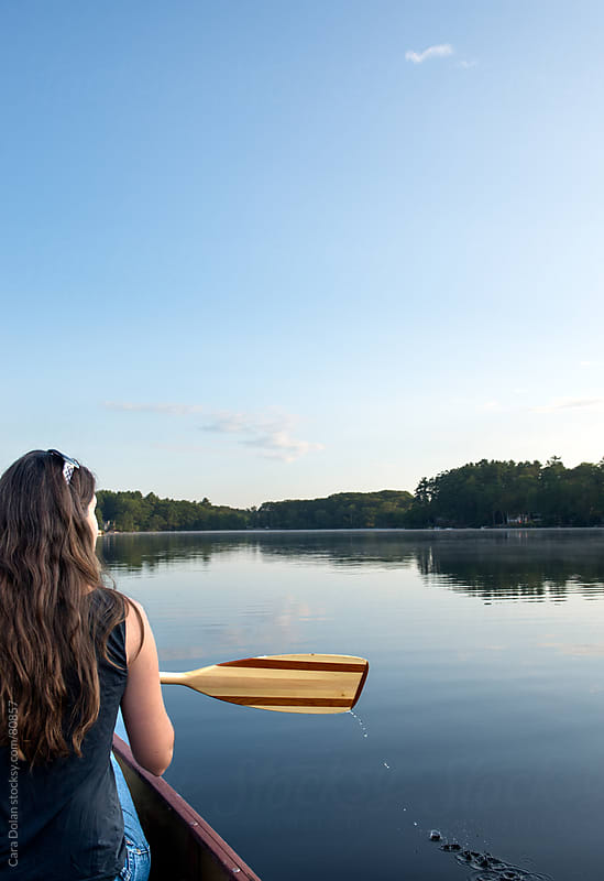Woman paddles a canoe on a lake at sunrise by Cara Dolan for Stocksy United