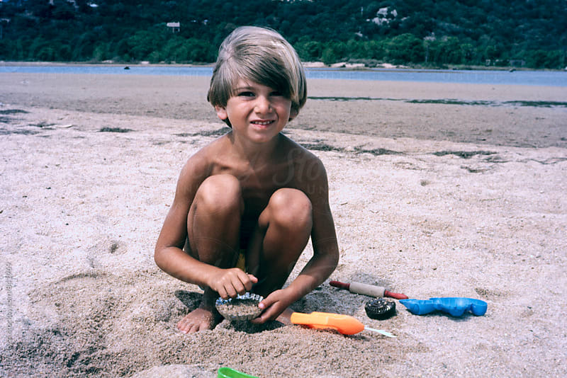 young boy play with sand by Juri Pozzi for Stocksy United
