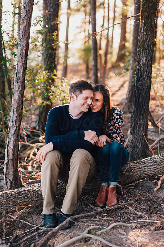 Happy Couple Sitting on a Log in the Woods by michelle edmonds for Stocksy United