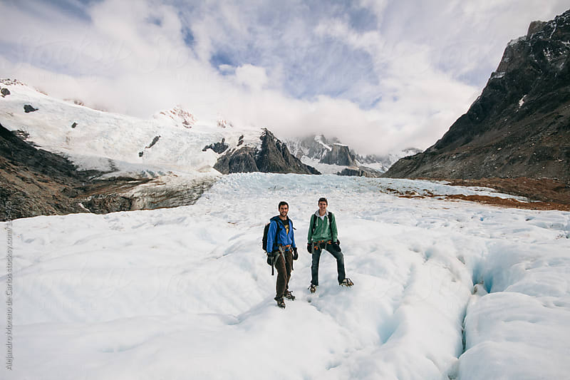 Two friends hiking with ice crampons a glacier by Alejandro Moreno de Carlos for Stocksy United
