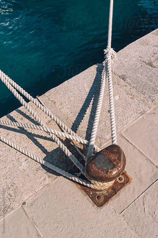 Close-up ropes tied on rusty bollard on pier by Trent Lanz for Stocksy United