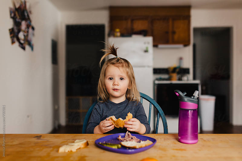 Cute toddler girl eating an orange at the kitchen table. by Jessica Byrum for Stocksy United