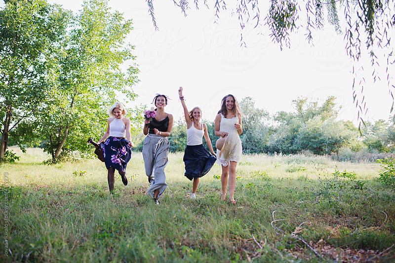 Happy female friends running in nature by Jovana Rikalo for Stocksy United