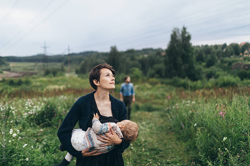 Beautiful family walking through countryside  by Evgenij Yulkin for Stocksy United