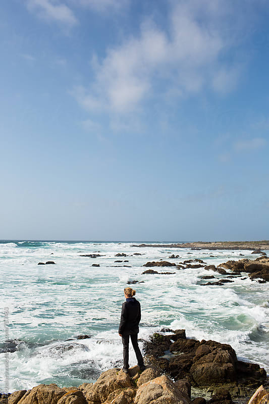 Woman standing on a rock on the coast of the Pacific Ocean by michela ravasio for Stocksy United