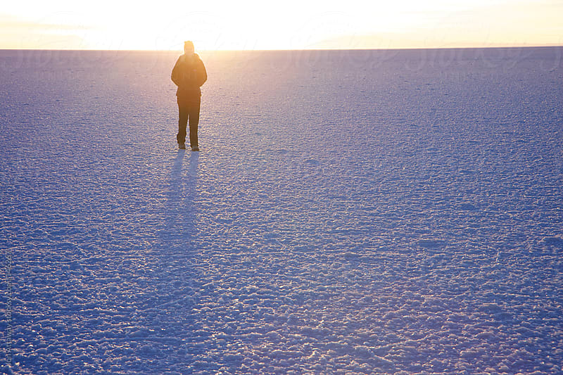 Young woman silhouetted on the Uyuni salt flat by Jon Attaway for Stocksy United