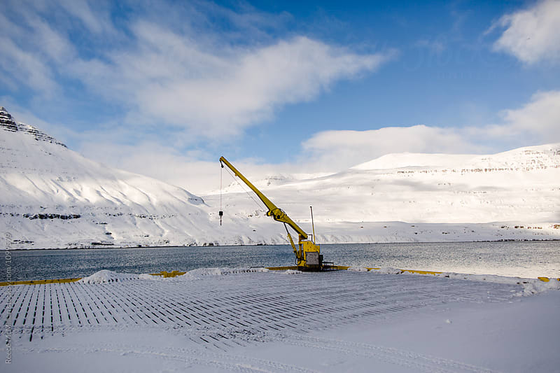 A crane on an Icelandic dock by Reece McMillan for Stocksy United
