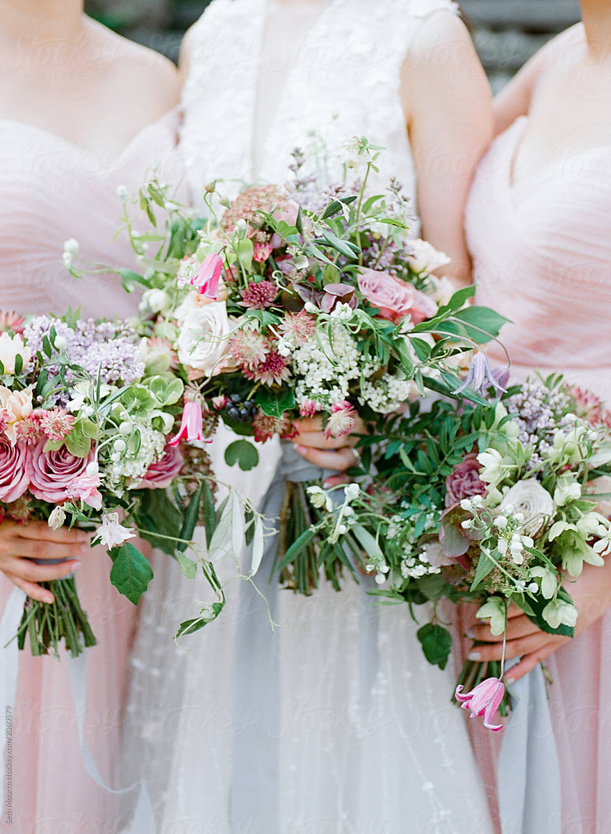 A Bride Amp Her Bridesmaids Hold Delicate Green Amp Pink Floral
