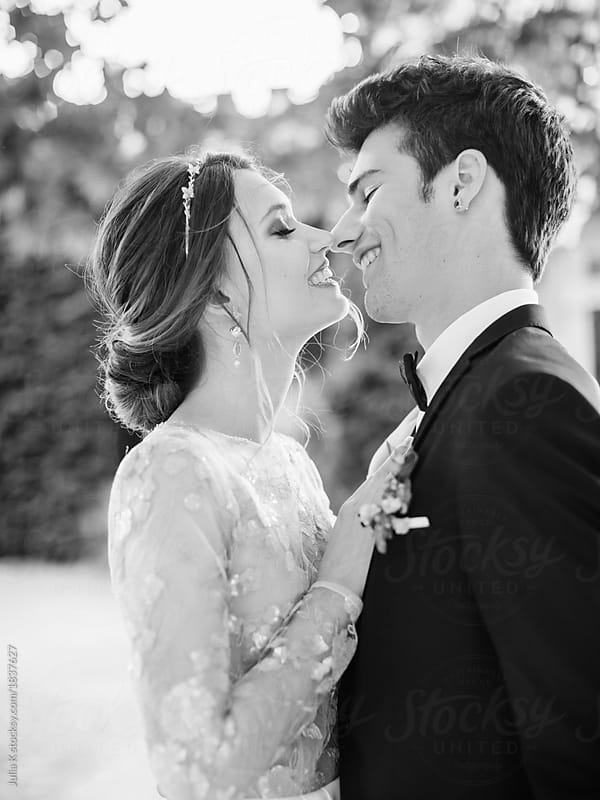 Cheerful newlywed couple with bouquet