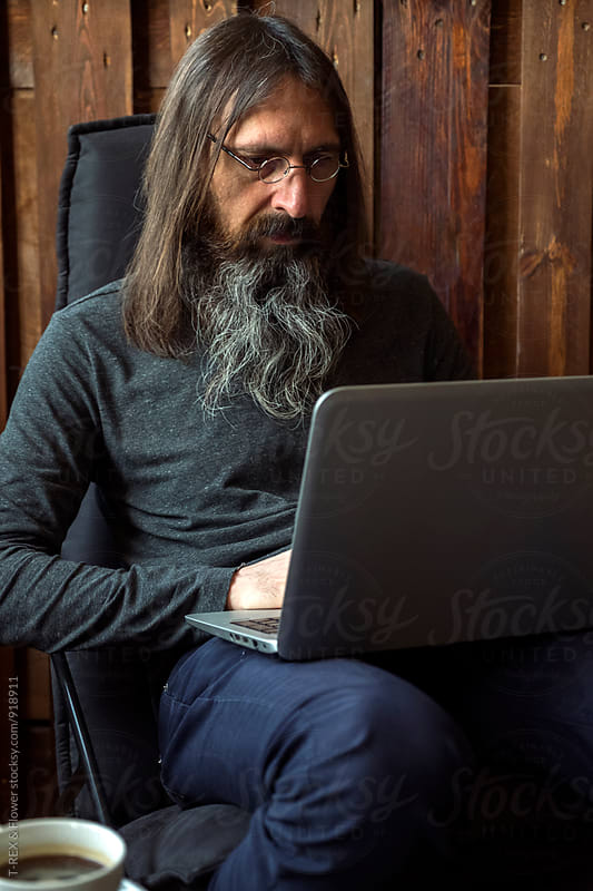 Long haired man sitting on chair while using laptop by T-REX & Flower for Stocksy United