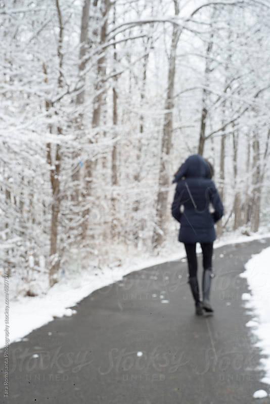 woman walking on a snowy day by Tara Romasanta for Stocksy United