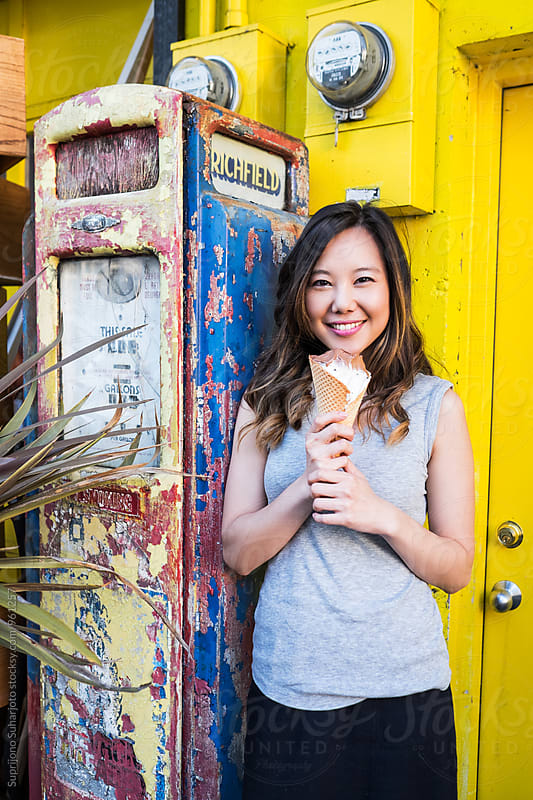 Asian woman outdoor holding an ice cream by Suprijono Suharjoto for Stocksy United