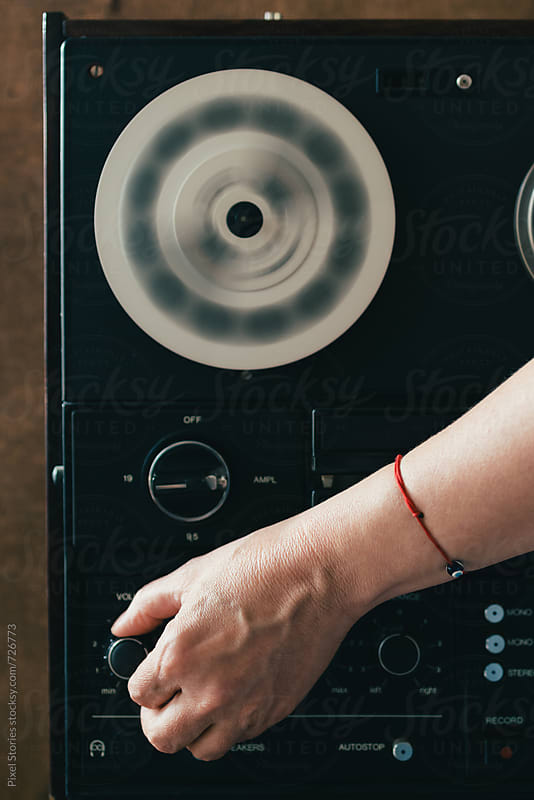 Female hand adjusting a knob on reel-to-reel tape recorder by Pixel Stories for Stocksy United