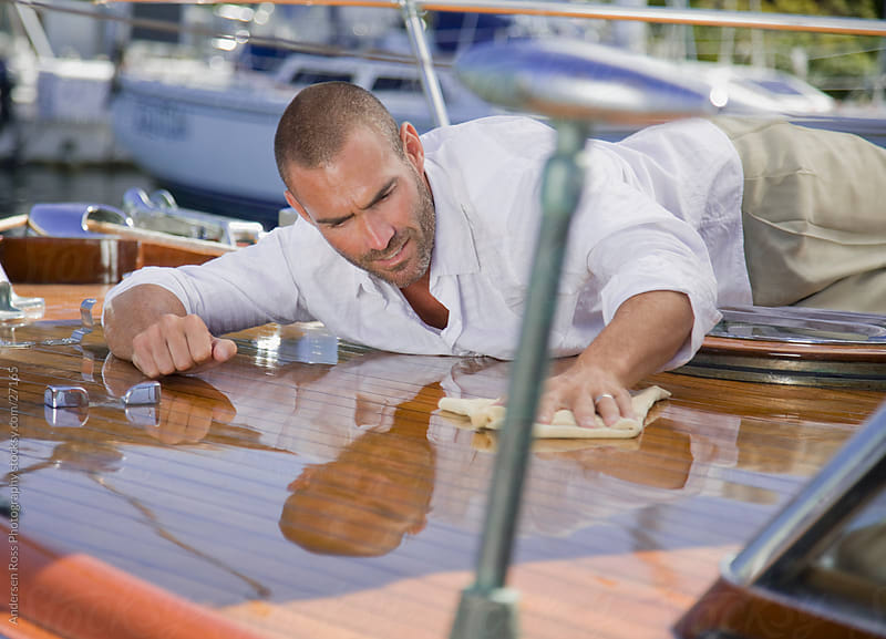 Man polishing boat by Andersen Ross Photography for Stocksy United