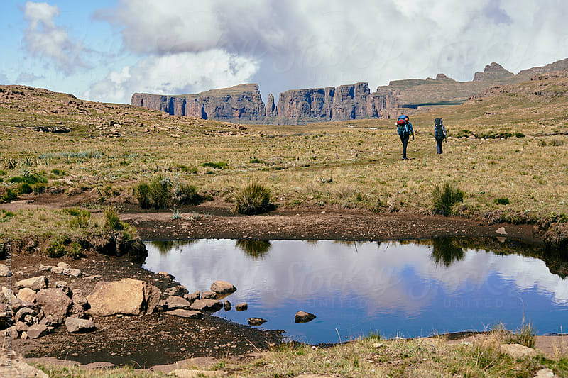 A pond reflecting cloud and sky with two hikers backpacking through mountains. by Jacques van Zyl for Stocksy United