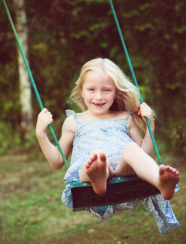 A blonde haired little girl with missing teeth on a swing by Helen Rushbrook for Stocksy United