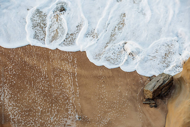 White foam of the sea getting to the sandy shore  by Alejandro Moreno de Carlos for Stocksy United