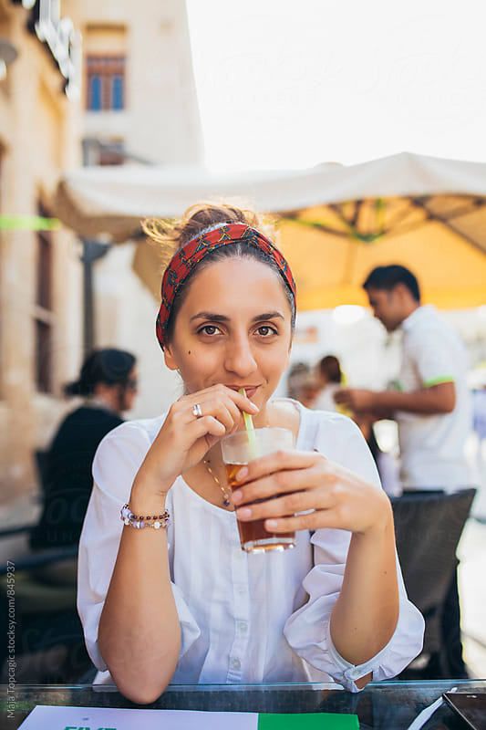 Woman drinking juice outdoors by Maja Topcagic for Stocksy United