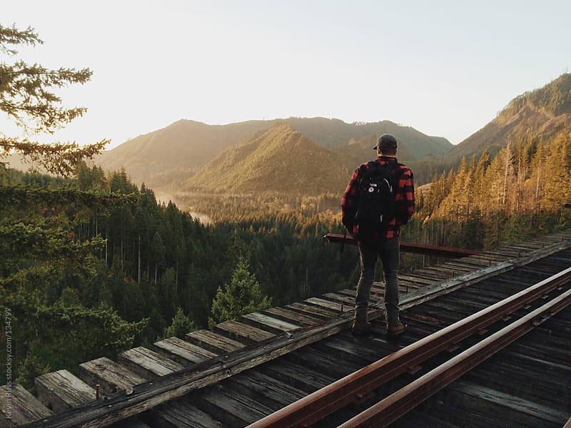 Man Walking on Train Bridge by Kevin Russ for Stocksy United