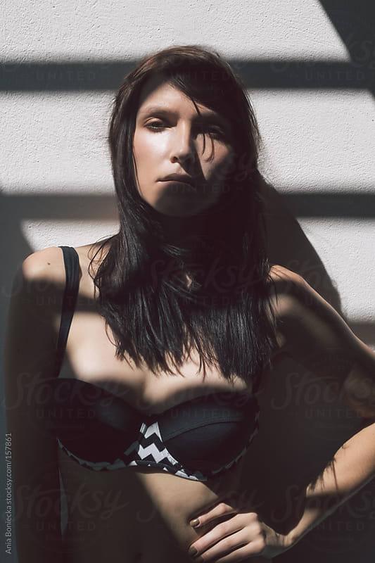 A beautiful woman in a black bikini standing in a shadow by Ania Boniecka for Stocksy United