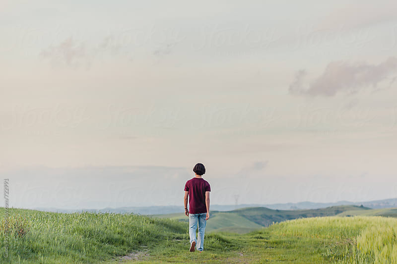 Back view of a teenage boy walking a long road through the fields in Italy by Cindy Prins for Stocksy United