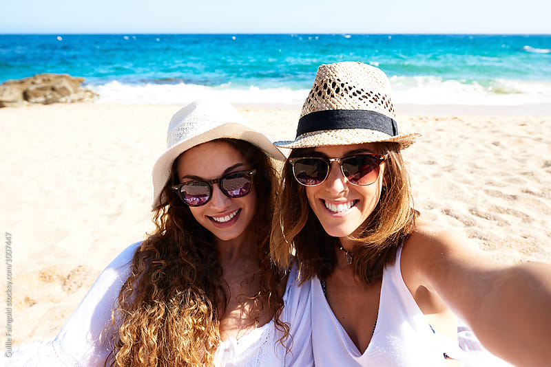 Two friends in sunglasses and hats smiling at camera by Guille Faingold for Stocksy United