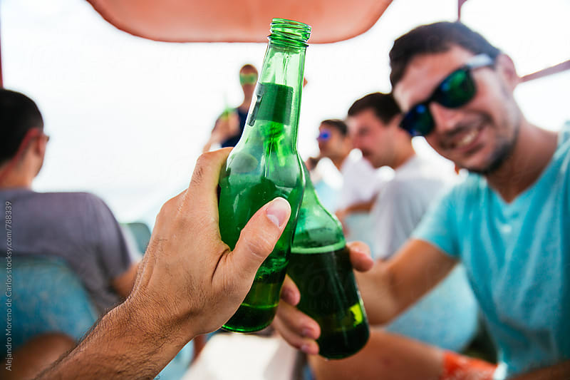 Front view of a man's hand holding a green beer bottle making a toast with a friend by Alejandro Moreno de Carlos for Stocksy United