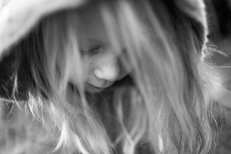 Little Girl with Freckles looking Down by Amanda Voelker for Stocksy United