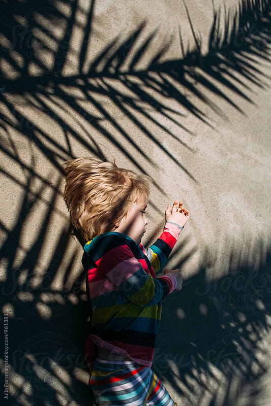 Little girl in bright clothes lies down on a pavement covered in palm tree shadows. by Julia Forsman for Stocksy United