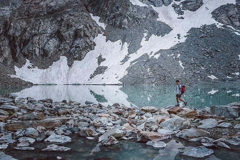 Hiker walking across a lake in mountain by GIC for Stocksy United