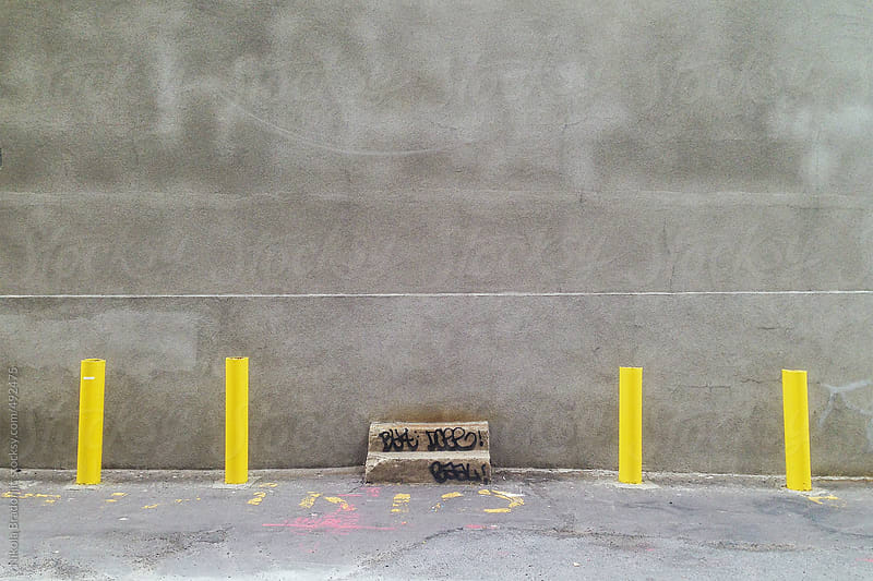 Gray wall with 4 yellow pole by Nikola Bradonjic for Stocksy United